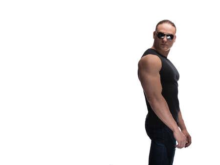 Portrait of a brutal man bodybuilder model in sunglasses on a white background