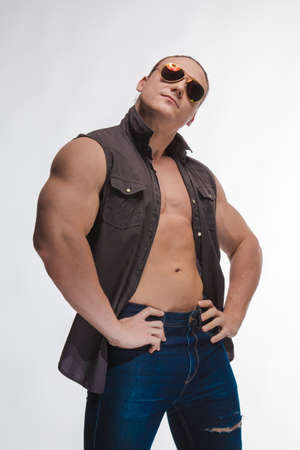 Portrait of a brutal man bodybuilder model with sunglasses on a white background 写真素材