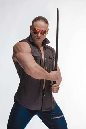 Portrait of a brutal man bodybuilder in sunglasses with a sword on a white background 写真素材