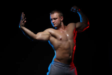 male bodybuilder athlete with naked torso posing against a black background, in red and blue light