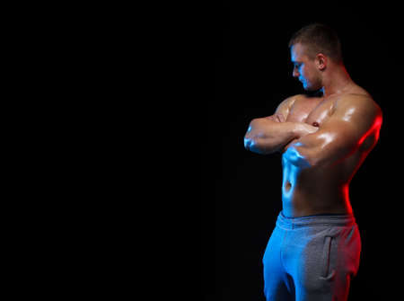 male bodybuilder athlete with torso posing against a black background, in red and blue light
