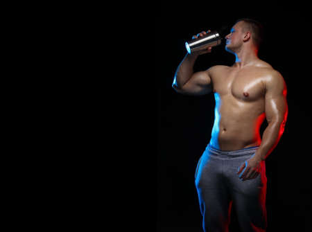 sportsman man bodybuilder with bare-chested with a shaker in hands on a black background, in red and blue light