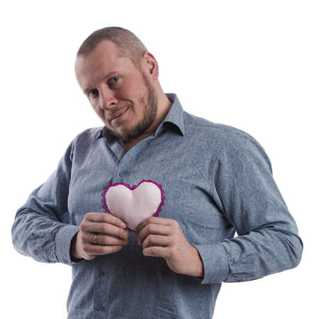 emotional actor man in a gray shirt with a soft toy heart in hands on a white background in studio