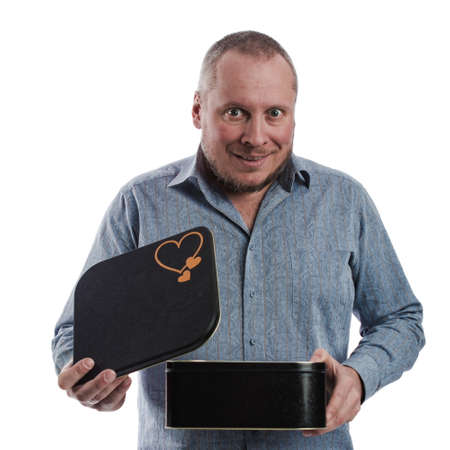 emotional actor man in a gray shirt with a large black box in his hands, on a white background in studio