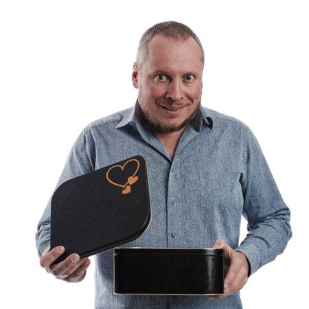 一名情绪激动的男演员穿着灰色衬衫,手里拿着一个大黑盒子,背景是白色