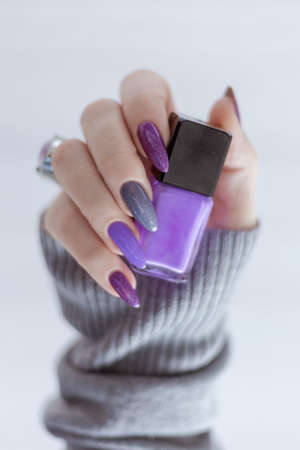 Female hand with lilac purple long nails and nail polish bottle