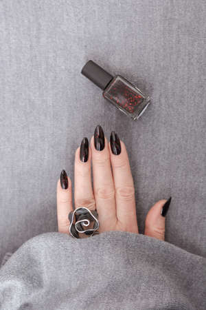 Woman's hands with long nails and gray black manicure with bottles of nail polish