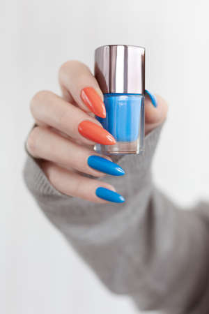 Female hand with long nails and multi-colored bright neon bottle manicure with nail polish and pen markers