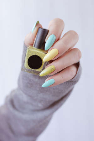 Female hand with long nails and multi-colored manicure, bottles of nail polishes Imagens