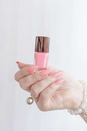 Female hand with long nails and a bottle of pink nail polish Imagens