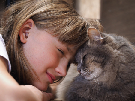 Bliss. Girl smiling cat, clinging to the animal and the girl lbom. Cat nice, big shot, only the face and muzzle cat Archivio Fotografico