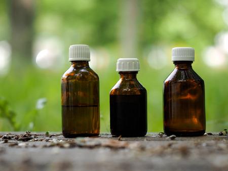 어두운 유리의 세 의료 병입니다. 자연 배경 - 흔적, 잔디입니다. 개념 - 허브, 아로마 테라피, 동종 요법을 기반으로 한 의약품 스톡 콘텐츠