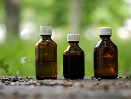 Three medical bottle of dark glass. Natural background - trail, grass. Concept - medicines based on herbs, aromatherapy, homeopathy