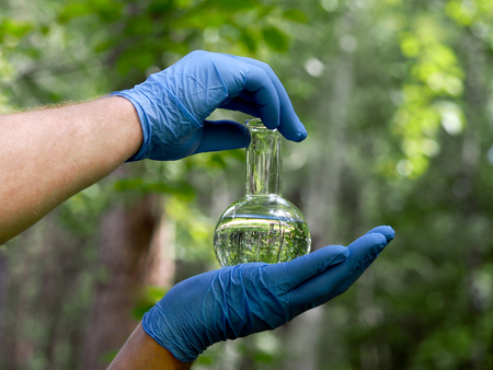 retort: Hands in gloves hold a retort with a transparent liquid. Natural background - grass, trees. In retort water, forests reflection. Concept - clean water, water quality, ecology, environment Stock Photo