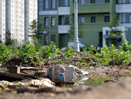 vacant lot: Rubbish, dirty puddles in a vacant lot near the buildings. Construction garbage. Concept - urban ecology, construction and environmental protection