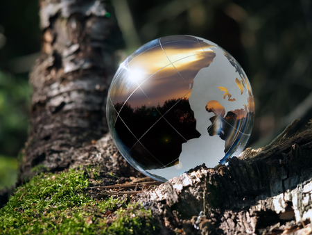 time zones: Transparent ball in the green forest. In the field of reflected sunset, sky, trees. Glass - a material, concepts and themes, time of day, environment, ecology, peace, raznovye time zones Stock Photo