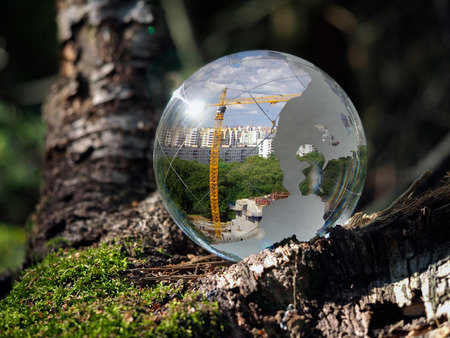 fragile peace: Ball Sphere in the woods on moss. Reflection - the city, crane, building metropolis. The concept of urban ecology, construction, nature protection Stock Photo