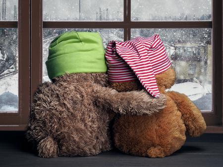 Deux amis regardant par la fenêtre la neige tomber et la ville. Jouets chapeaux colorés oursons. Embrassez la fenêtre. Concept - l'amour, l'amitié, le soutien Banque d'images - 61500355