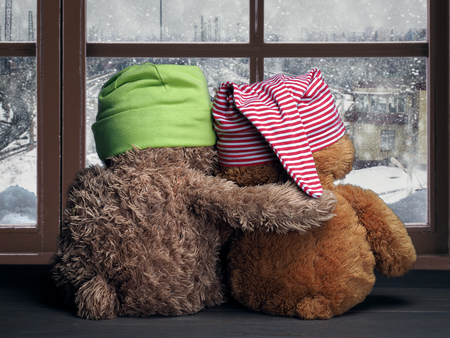 Two friends looking out the window at the falling snow and the city. Toys colorful hats bear cubs. Embrace the window. Concept - love, friendship, support
