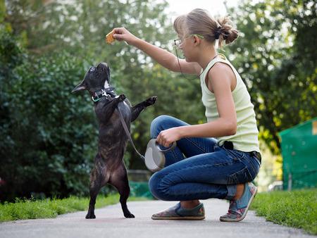 Fille marchant un chien et de former. Puppy sauter de plaisir. Rue de la ville, l'été. Bouledogue français en noir