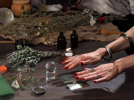 Work hereditary Sage. Find people on photos. Hands witch. working table magician. Photo missing person. The magic transparent sphere. Many medicinal herbs. Magic, estransensorika, occult, magic Stock fotó - 61500366