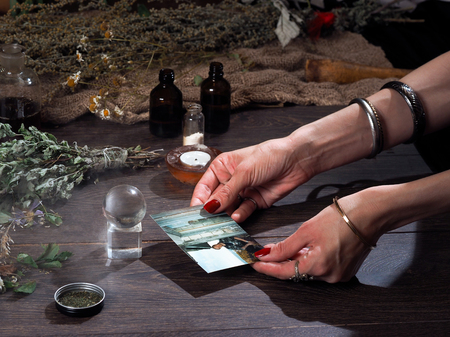occult: Work hereditary Sage. Find people on photos. Hands witch. working table magician. Photo missing person. The magic transparent sphere. Many medicinal herbs. Magic, estransensorika, occult, magic
