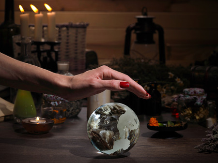sorcery: Hands witch. Transparent sphere. Magical objects and utensils of the alchemist. Candles, herbs. Concept - alternative medicine, witchcraft and the occult. Halloween. Divination, sorcery. Work Healer