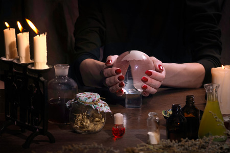 divination: Hands witch. Transparent sphere. Magical objects and utensils of the alchemist. Candles, herbs. Concept - alternative medicine, witchcraft and the occult. Halloween. Divination, sorcery. Work Healer