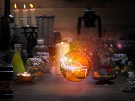 paranormal: Golden Sphere. Magic items. Flasks, retort for alchemy. Beautiful glow. Concept - the magician, mystic, paranormal phenomena. Occult, esoteric, spiritualism, calling the spirits and ghosts Stock Photo