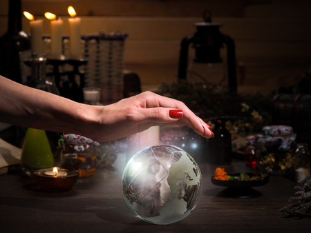 esoterismo: Female hand on the magic sphere. Silhouette of a ghost in a bowl. Flasks, retort for alchemy. Concept - occult, esotericism, spiritualism, calling the spirits and ghosts, underworld