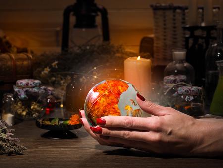 esoterismo: Mujer mano que sostiene una esfera de fuego mágico. El brillo dorado. Frascos, replican para la alquimia. Concepto - oculto, esoterismo, el espiritismo, llamando a los espíritus y fantasmas, bajo mundo Foto de archivo
