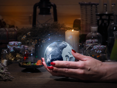 Womens hands holding the magic sphere with the stars. The blue glow. Flasks, retort for alchemy. Concept - the world of astrology, stars, prediction, occult, spirituality, spiritualism