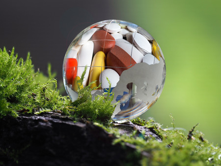 is based: A huge ball of medicine tablets lying on the moss. Concept - medicine based on natural ingredients, homeopathy, alternative treatments