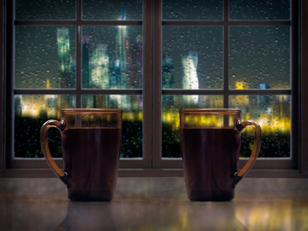 window sill: Two mugs with a hot drink - tea or coffee on the window sill of the window. Outside, the night, the city lights, rain, drops on the glass