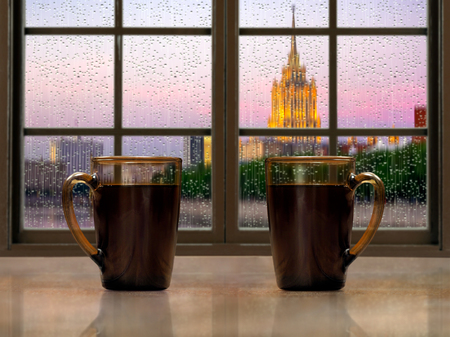 window sill: Two mugs with a hot drink - tea or coffee on the window sill of the window. During the early morning, the city, the rain. Concept - good morning alertness, awakening together