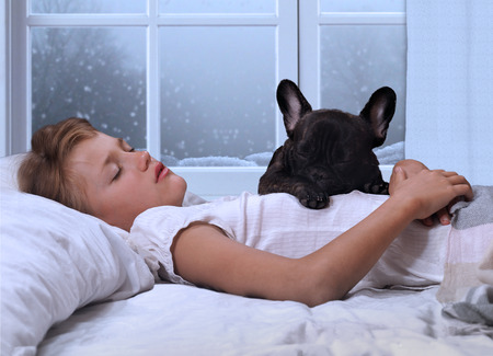 without windows: The young girl the teenager and a dog sleeping in the bed. Sound sleep, early morning. Winter, the snow outside the window