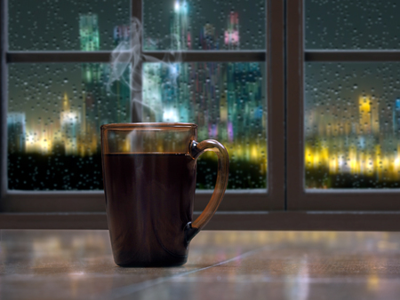 A mug with a hot drink - tea or coffee on the window sill of the window. Outside, the night, the city lights, rain, drops on the glass Stok Fotoğraf
