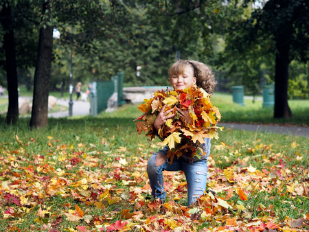 Portrait of a beautiful young teen girl with a bunch of autumn leaves in the park Stock Photo
