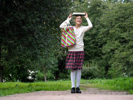 Funny and happy schoolgirl in school uniform in a park holding a book on his head and laughs Stock Photo