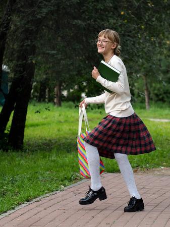 marca libros: Divertida y feliz colegiala en uniforme escolar en el parque divirtiéndose