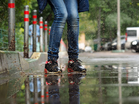 wet jeans: Human Legs in jeans and sneakers in a puddle. Splashes of water. Run, jump in puddles