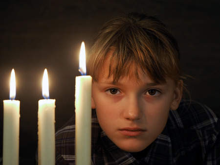The face of a beautiful girl, and three burning candles. Portrait Stock Photo