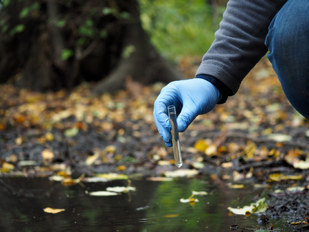 Water sample. Hand in glove collects water from a puddle in a test tube. Analysis of water purity, environment, ecology - concept. Water testing for infections, harmful emissions