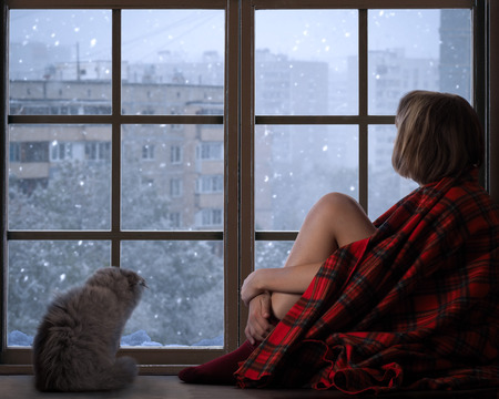 window sill: The girl and a cat sitting on the window sill of the window and looking at the falling snow. The concept of home comfort, season, solitude