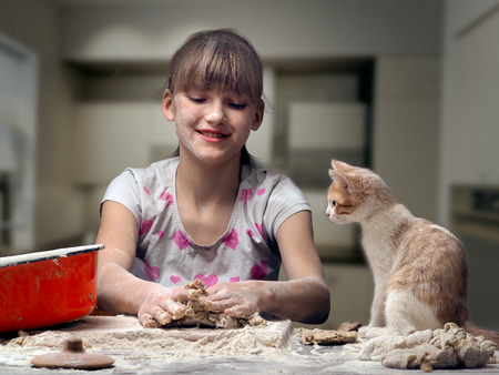 Funny girl kneads dough. kitten sitting next to. The girl, a cat and a table - all in flour