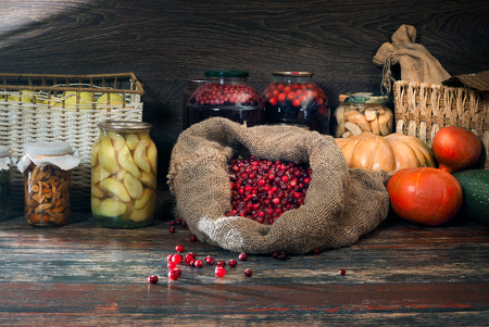 Autumn Still Life with a sack of fresh berries cranberries forest, banks with canned berries, fruits, vegetables and pumpkins. Storage inventories for the winter harvest, vitamins Stok Fotoğraf