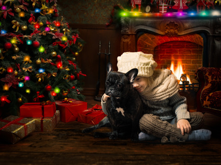 Cute and happy child with a dog in a Christmas tree. New Year's interior in the room, fireplace Banque d'images