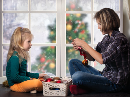 Children are preparing for the New Year, Christmas. Girls sit at the window and consider Christmas decorations. Outside the window Christmas tree, snow