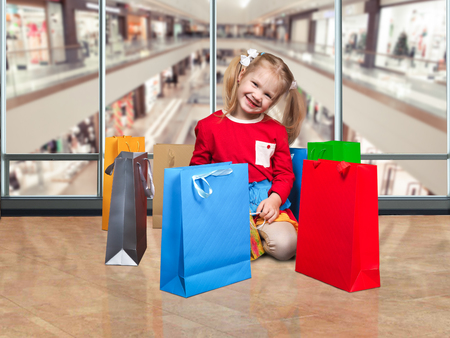 affordable: Happy little girl and lots of colorful shopping bags. Shopping center. Concept - the purchase, sale, goods for children, shopping