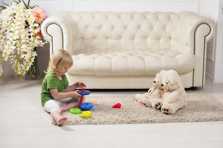 Educational game is to collect colored rings of the pyramid in order. The child collects the constructor pyramid, sitting together with toys on the floor, on the carpet. Baby barefoot Stock Photo